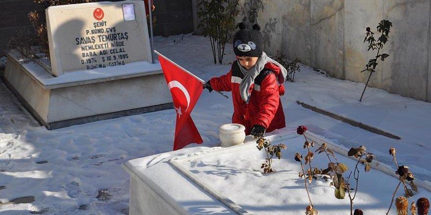 'Şehitler üşümesin' diye mezar taşındaki karları temizledi