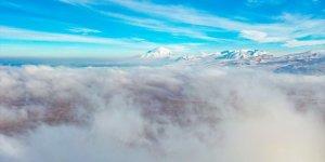 Iğdır'da sis, üstüne çöktüğü karlı dağların güzelliğine güzellik kattı