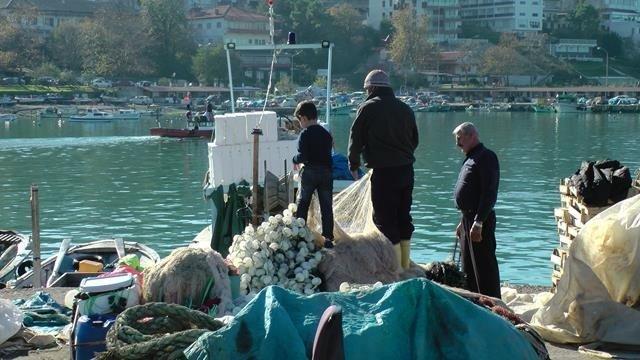 Balıkçılar ağlarını onarıyor